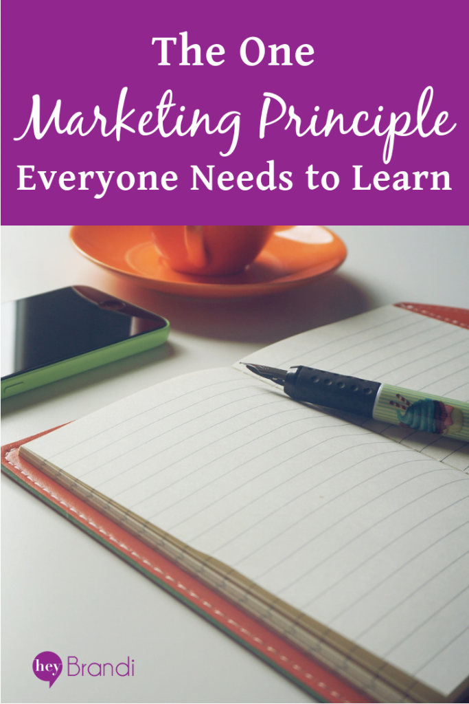The One Marketing Principle Everyone Needs to Learn - pen laying on notebook with orange cup of tea.